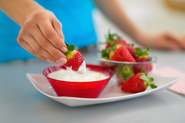 Closeup on happy young woman eating strawberry with yogurt