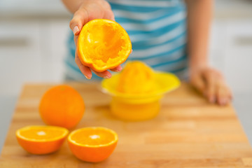Closeup on young woman showing orange peel after squeezing juice