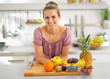 Portrait of young housewife with fruits in modern kitchen