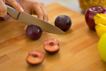 Closeup on young housewife cutting plums
