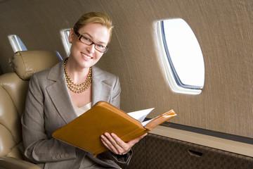 Businesswoman with folder on aeroplane, smiling, portrait