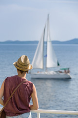 Female passenger on the deck of the ferry watching the sailboat