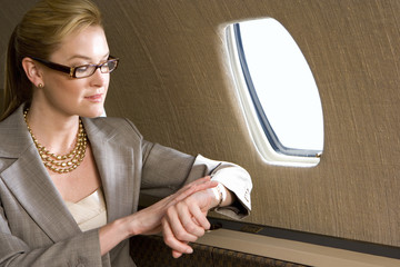 Businesswoman looking at watch on aeroplane, close-up