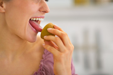 Closeup on young housewife eating kiwi