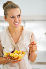 Portrait of happy young housewife mixing fruit salad