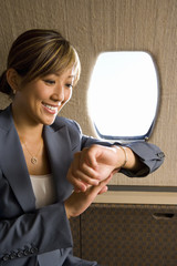 Businesswoman looking at watch on aeroplane, smiling, close-up