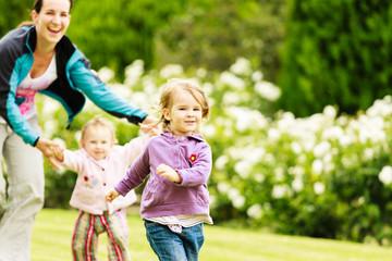 Mutter spielt mit zwei kleinen Töchtern auf einer Wiese im Park