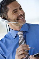 Businessman wearing telephone headset, using personal electronic organiser, smiling, close-up (tilt)