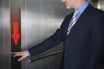 Businessman pushing down arrow on elevator