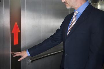 Businessman pushing up arrow on elevator