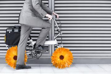Businessman riding bike with flower wheels