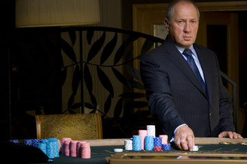 Mature man gambling, hand on chips, portrait