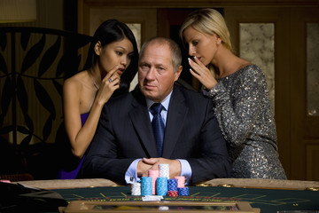 Mature man with gambling chips at poker table, flanked by young women whispering, portrait