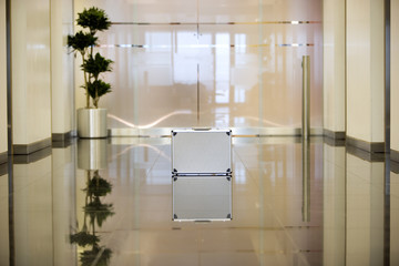 Reflection of silver briefcase on shiny lobby floor
