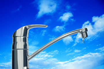 Shiny faucet on a background of blue sky