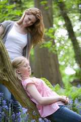 Mother watching daughter relax on tree trunk in forest