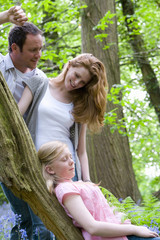 Mother and father watching daughter relax on tree trunk in forest