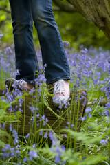 Girl balancing on log among bluebell flowers