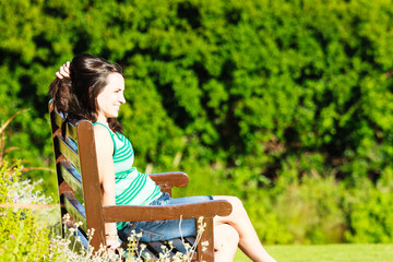 Junge Frau entspannt auf Parkbank