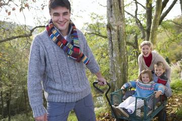 Portrait of man pulling children and wife in wheelbarrow