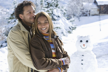Mixed race couple hugging in snow, snowman in background