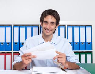 Mann mit schwarzen Haaren sortiert Post im Büro