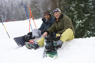 Men sitting in snow on ski vacation