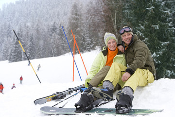 Mid adult couple sitting in snow on ski vacation