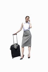 Businesswoman with luggage on mobile phone, cut out
