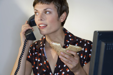 Businesswoman eating sandwich, using telephone, smiling