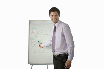 Businessman standing beside whiteboard, giving presentation, cut out