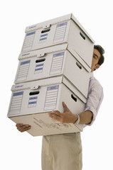 Businessman carrying stacked file boxes, face obscured, low angle view, cut out