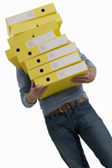 Businessman carrying stack of yellow folders, low angle view, cut out