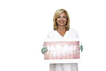 Female dentist holding large photograph of teeth, smiling, portrait, cut out
