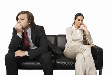 Anxious businessman and businesswoman sitting on sofa, cut out