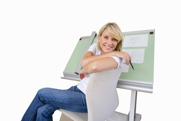 Woman sitting by blue prints on drafting board, smiling portrait, cut out