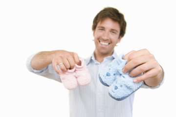 Young man holding baby slippers, smiling, cut out
