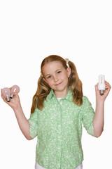 Girl holding up light bulbs, portrait, cut out