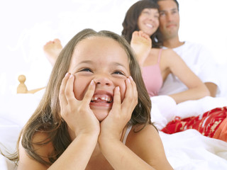 Girl in bed with parents, smiling, close-up, cut out