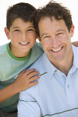 Boy embracing father, smiling, portrait, cut out