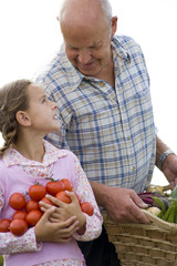 Grandfather and granddaughter with tomatoes and vegetables, cut out