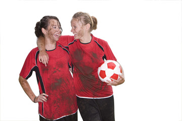 Muddy teenage girls laughing and holding soccer ball, cut out