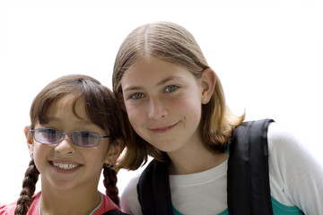 Two girls standing side by side, smiling, front view, portrait, cut out
