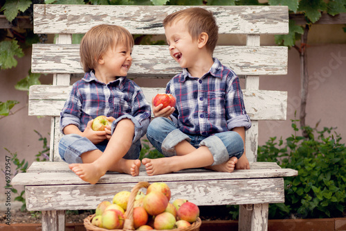 Two boys, sitting on a bench, eating apples and having fun - 69329547