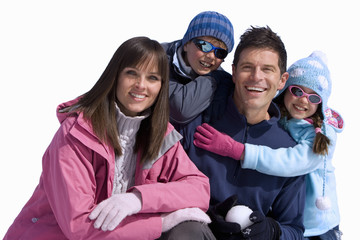 Family of four wearing winter clothing, smiling, portrait, cut out