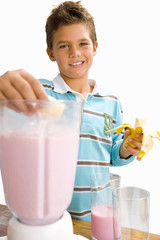 Boy making fruit smoothie, smiling, portrait, cut out