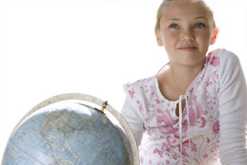 Girl sitting by globe, smiling, close-up, cut out