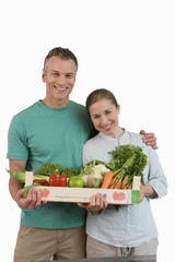 Couple with box of vegetables, smiling, portrait, cut out
