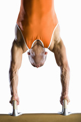 Male gymnast performing handstand on pommel horse, close-up, cut out