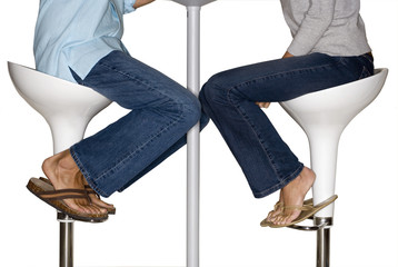 Couple sitting on stools, side view, low section, cut out